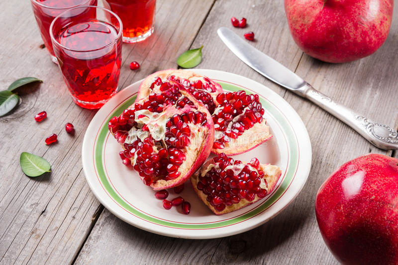 Whole and broken red ripe juicy pomegranates on rustic wooden unpainted table royalty free stock photo