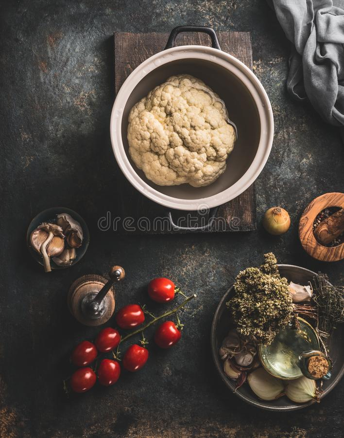 Whole cauliflower in cooking pot on dark rustic kitchen table background with vegetarian ingredients.Top view royalty free stock images