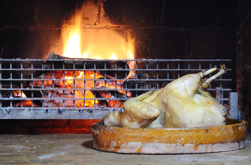 Whole chiken near the fireplace on dish. One chiken near the fireplace on dish. Christmas time stock photo