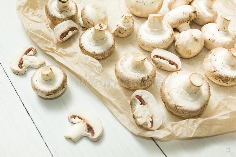 Whole and chopped white mushrooms on a white wooden background royalty free stock images