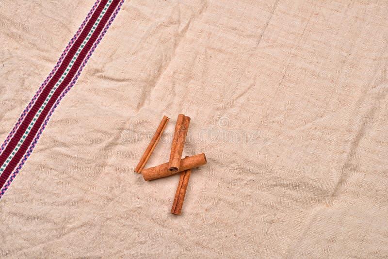Whole cinnamon sticks on background of jute fabric stock photo
