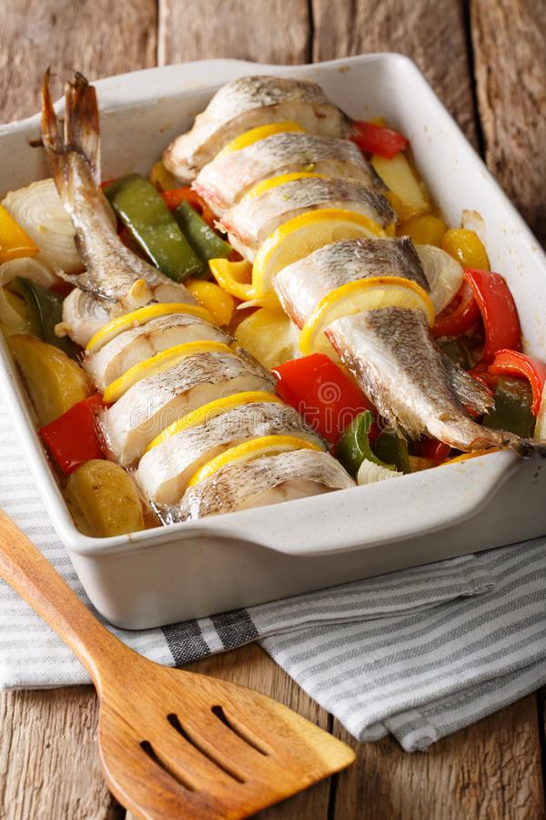 Whole cod baked with pepper, tomatoes, onions and lemon in a baking dish close-up. vertical stock photo