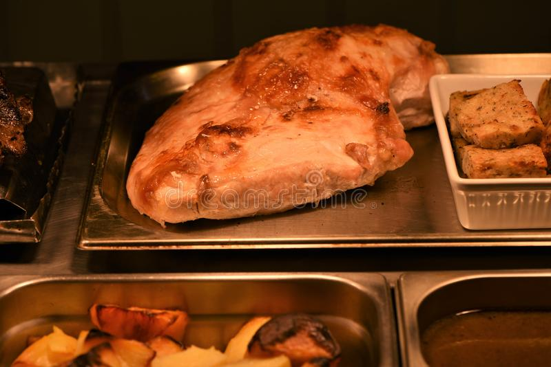 Whole cooked golden roast turkey breast with stuffing and gravy taken in a restaurant royalty free stock images