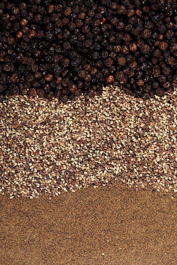 Whole, crashed and ground black peppercorns stock photo