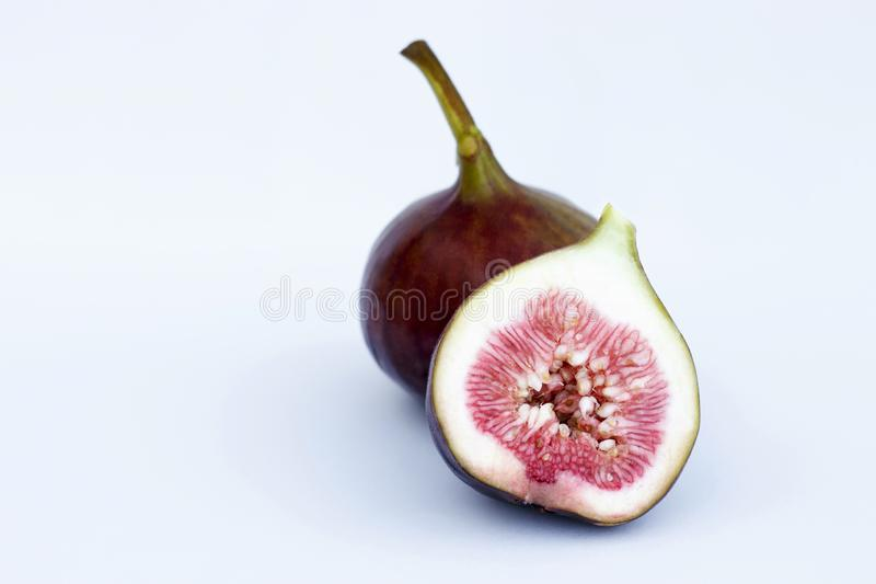 Whole and cut figs close-up isolated on a blue background royalty free stock photos