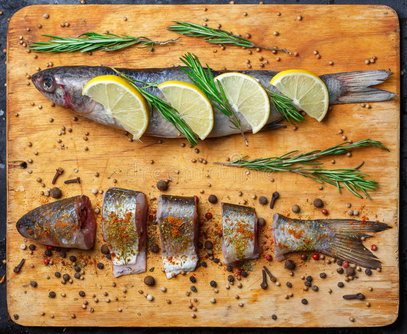 Whole and cut grey mullet fishes lie on light wooden cutting boa. Rd with lemon segments, rosemary branches, peppercorns, paprika, chilli pepper and other spices stock photos