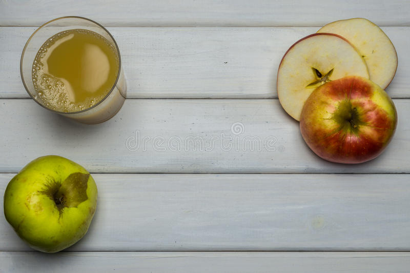 Whole and cut red and green ripe apples autumn harvest and apple juice, from above on white wooden table royalty free stock photo