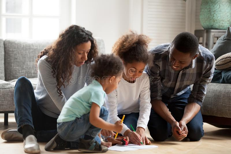 Whole family sitting on floor and drawing. Happy black African family sitting on a warm wooden floor have a fun spend free time together in living room at home stock photo