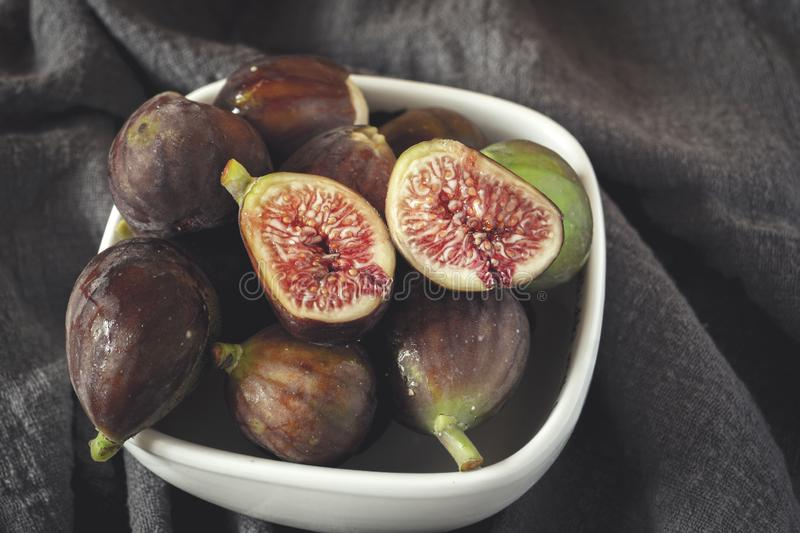 Whole figs and one fig sliced in half. On top of a table royalty free stock image