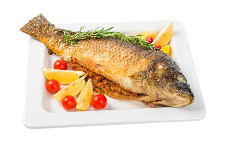 Whole fish carp baked in a dish with lemon, cherry tomatoes and rosemary isolated on white background. Close up stock photo