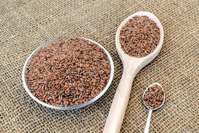 Whole flax seeds in a glass saucer, large wooden spoon and small metall spoon on a sackcloth background. Healthy food. For lower cholesterol and preventing royalty free stock images