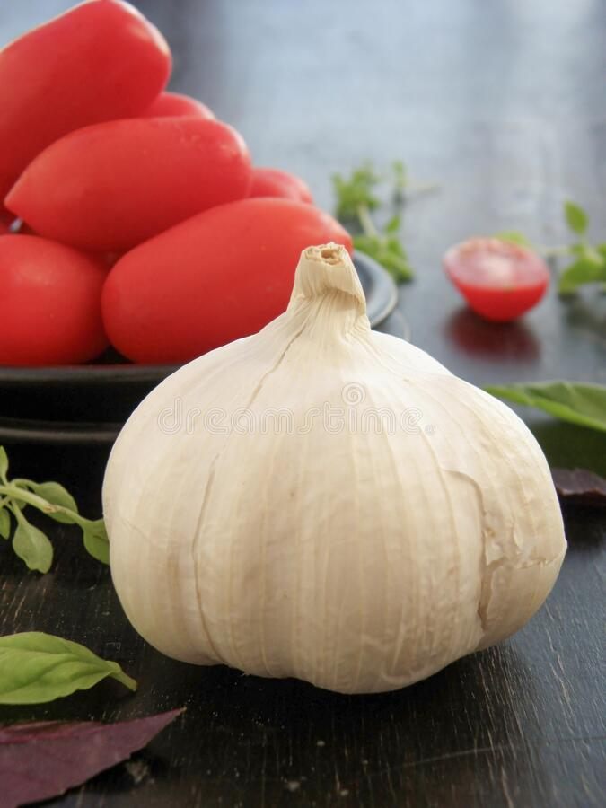 Whole garlic and tomatoes in the background royalty free stock image