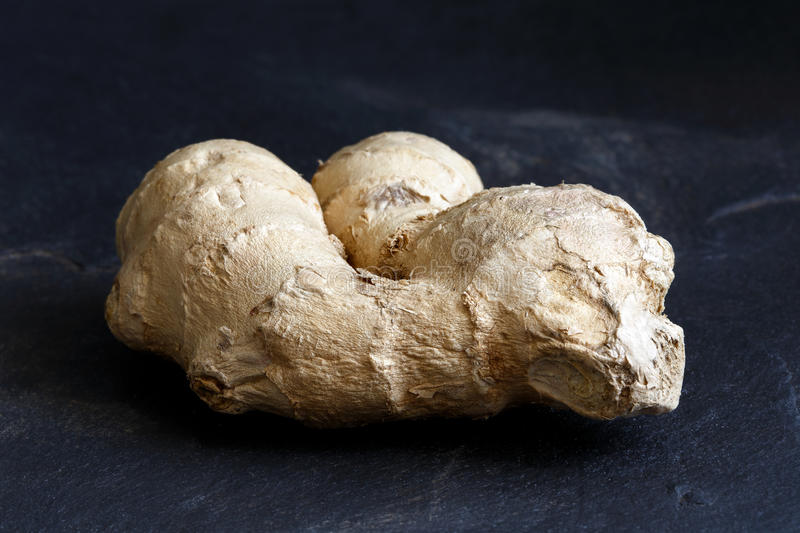 Whole ginger root on black slate. stock photography