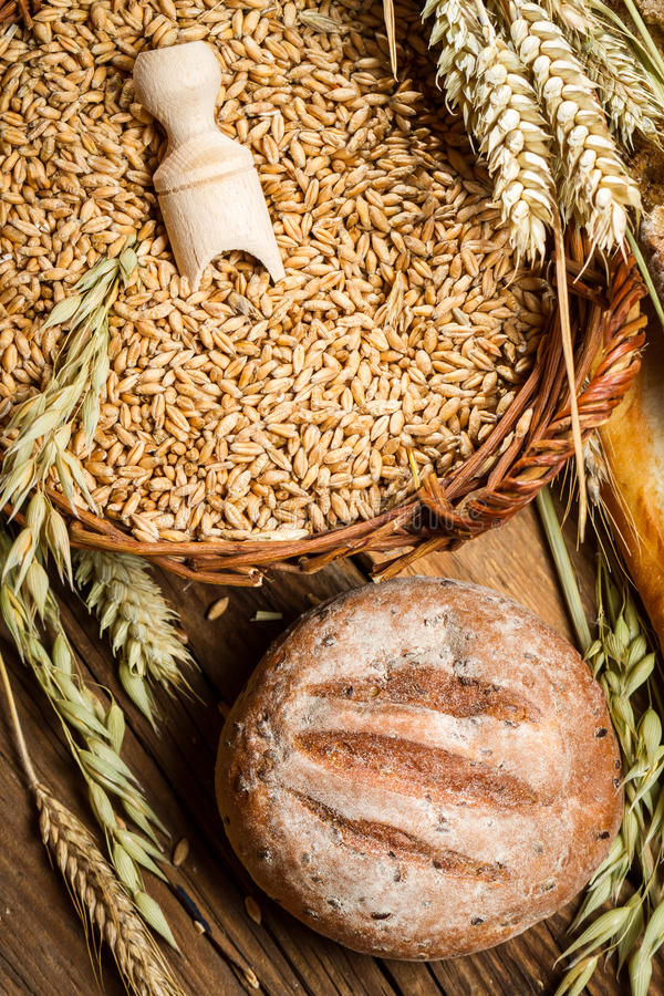 Whole grain bread with a basket full of grains royalty free stock images