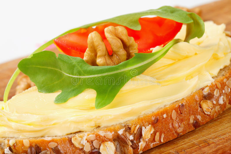 Whole grain bread with butter. Slice of whole grain bread with butter and walnuts stock photo