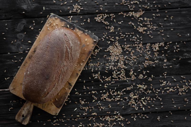 Whole grain bread is lying on a wooden table. Wheat grains are scattered nearby royalty free stock images