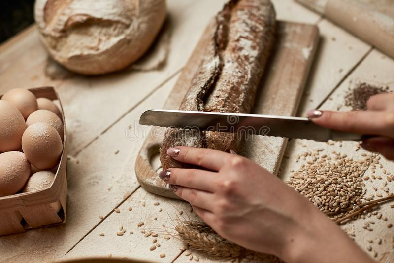 Whole grain bread put on kitchen wood plate with a chef holding gold knife for cut. Fresh bread on table close-up. Fresh bread on. The kitchen table royalty free stock photos