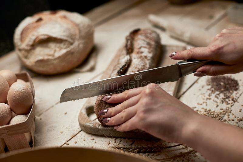 Whole grain bread put on kitchen wood plate with a chef holding gold knife for cut. Fresh bread on table close-up. Fresh bread on. The kitchen table stock image