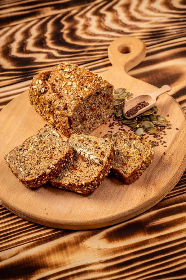 Whole grain bread with seeds of goji berry, pumpkin, flax and hemp, vertical image. space for text. top view stock photos
