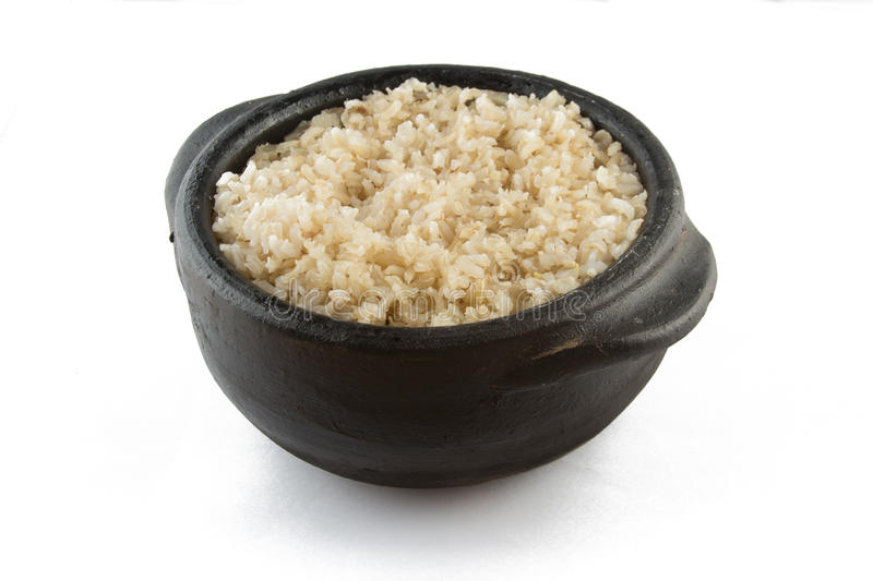 Whole grain brown rice cooked. Integral. Whole grain brown rice cooked into a pan isolated on white background. Integral royalty free stock photo