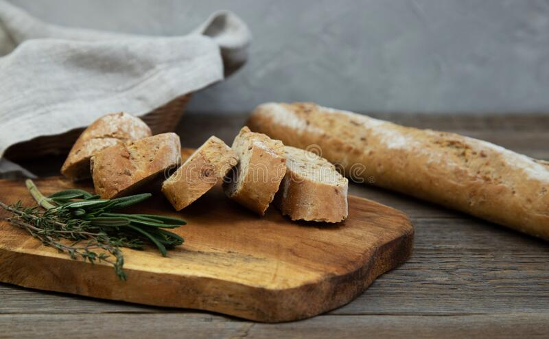 A whole-grain chopped baguette with herbs lies on a wooden board, next to a fresh sprig of thyme and rosemary herb. In the royalty free stock photo