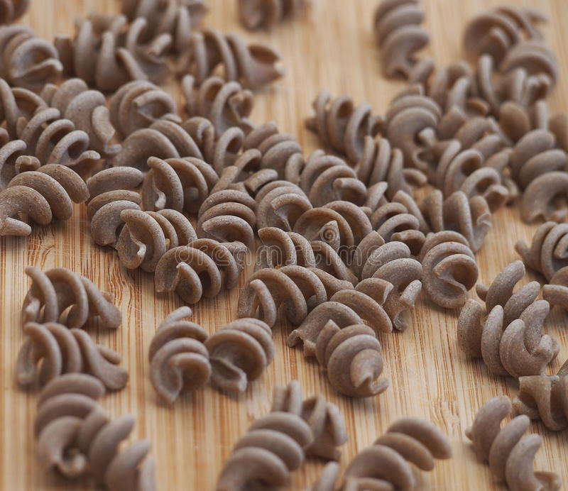 Whole grain eggless rye pasta (fusilli). On a wooden board royalty free stock images