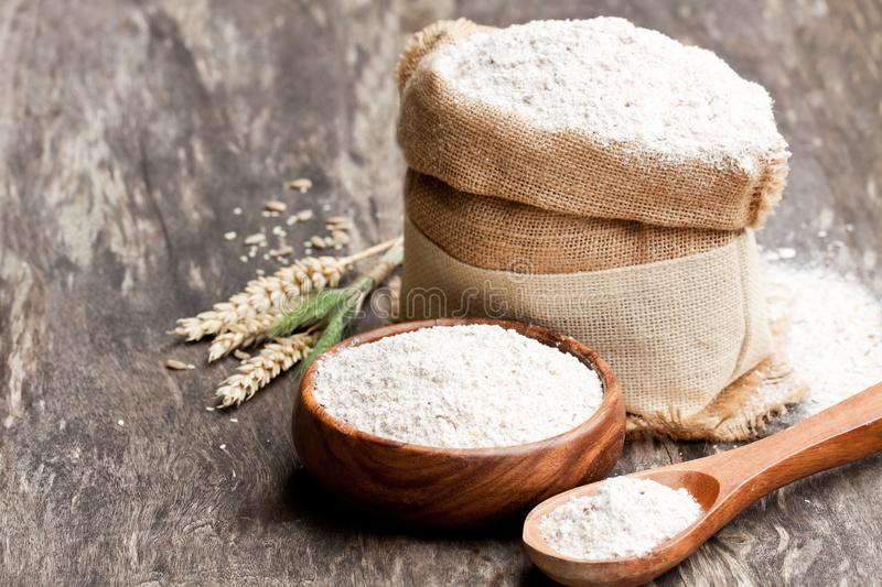 Whole grain flour in a wooden bowl and sackcloth bagwith ears royalty free stock photography