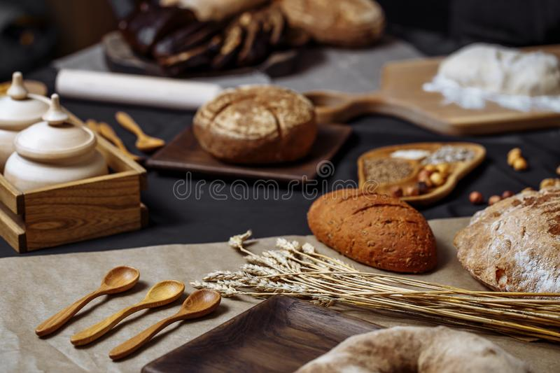 Whole grain multigrain bread, whole and sliced, contains seeds isolated on black royalty free stock image