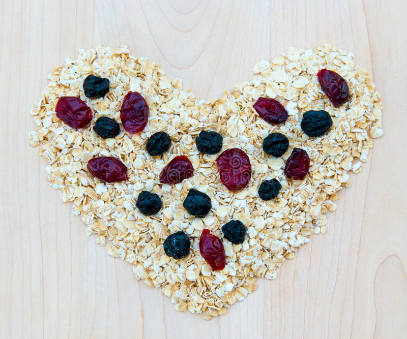 Whole grain oats with dried cranberries and blueberries in heart stock photos