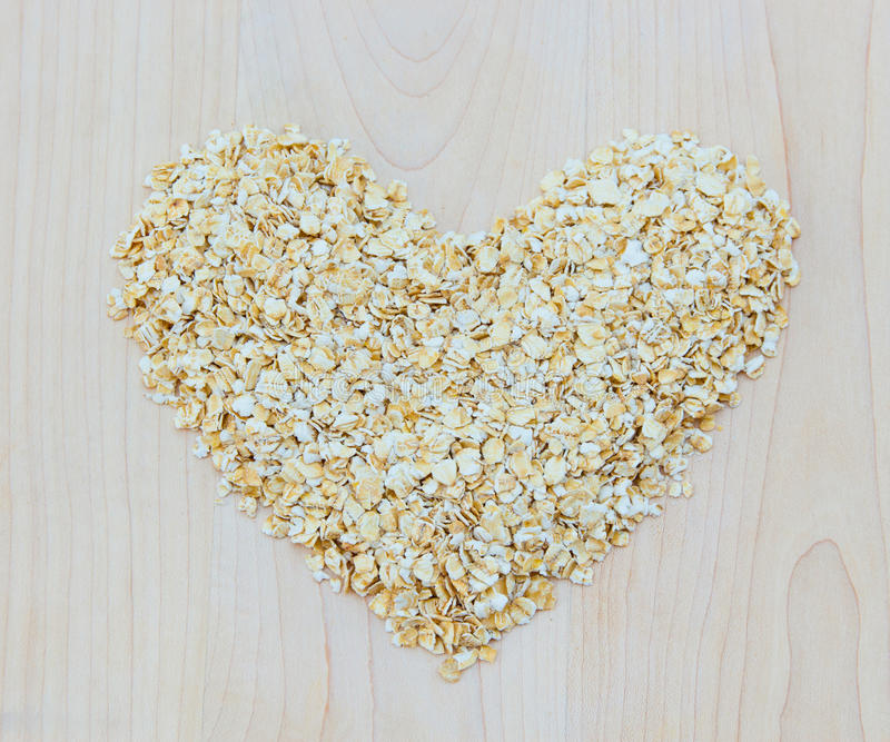 Whole grain oats in heart shape on wooden board royalty free stock photography