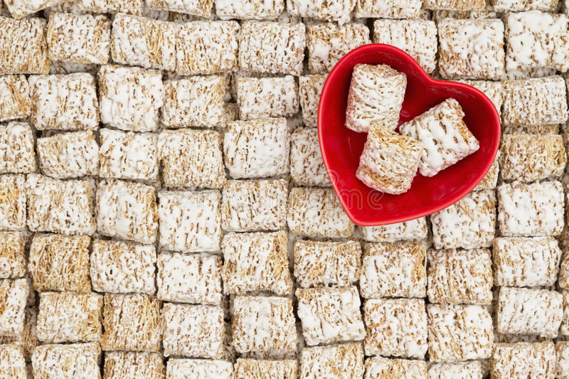 Healthy whole grain cereal background with a heart bowl. Whole grain wheat cereal with a red heart shaped bowl for a healthy cereal background stock photo