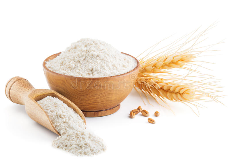 Whole grain wheat flour and ears isolated on white stock photography