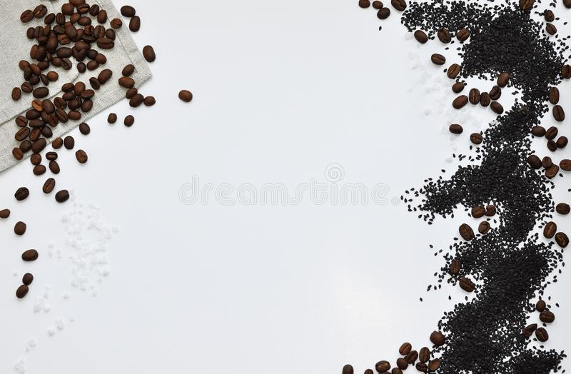 Whole grains of roasted black coffee scattered on a linen towel royalty free stock photography