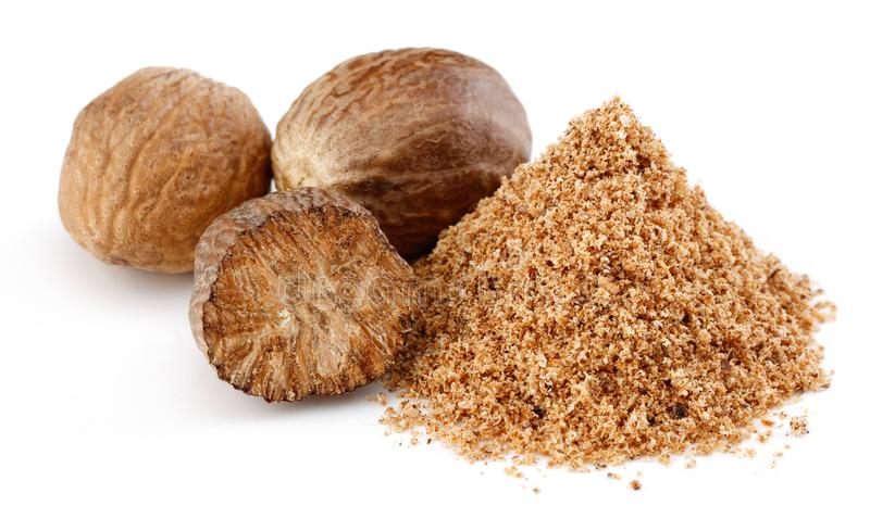 Whole and grated nutmeg on white royalty free stock image