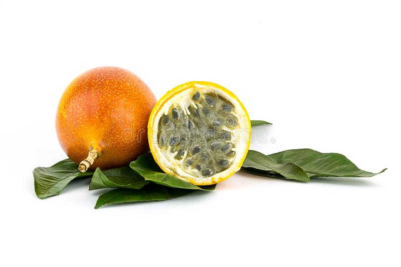 Whole grenadilla yellow passion fruit half of the fruit with a juicy filling with many seeds royalty free stock photography