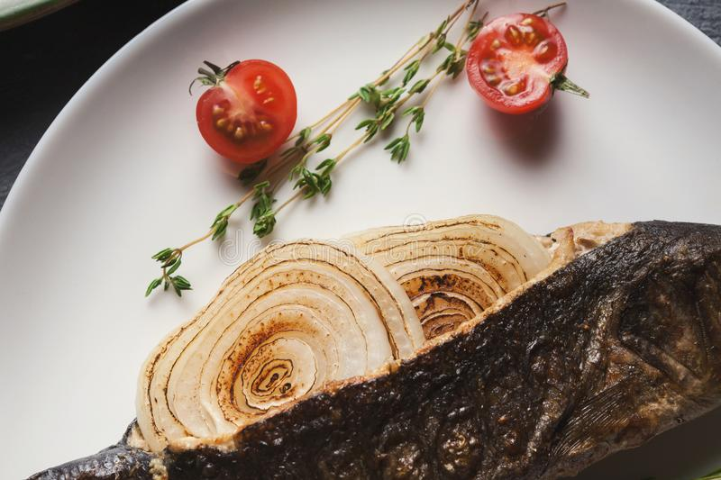 Whole grilled bass with onion on white plate royalty free stock photography