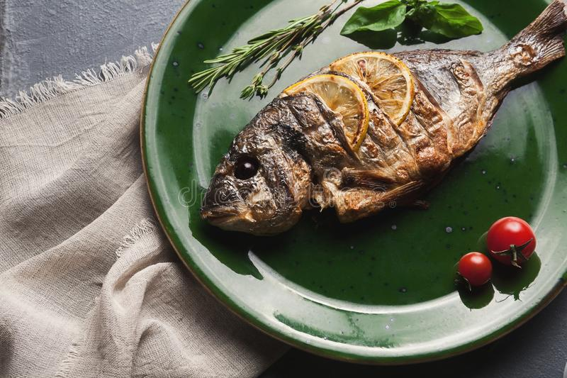 Whole grilled dorado with lemon slices on plate royalty free stock photography