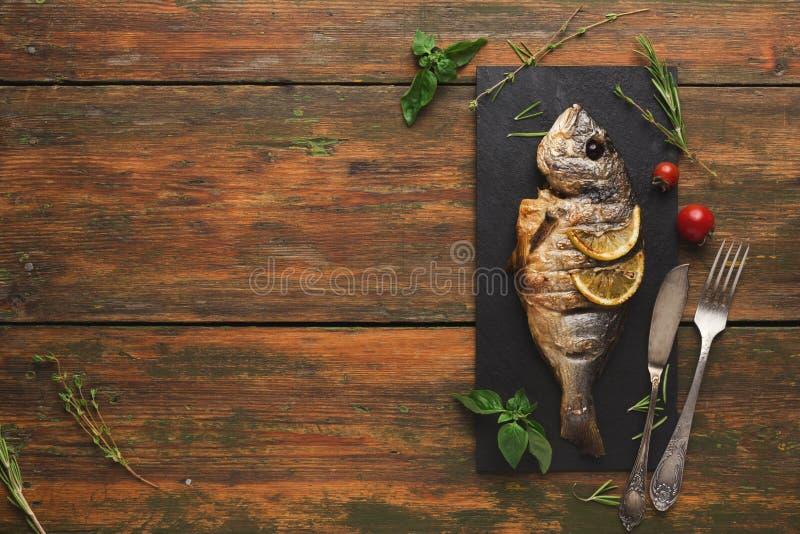 Whole grilled dorado with lemon slices on wood stock image