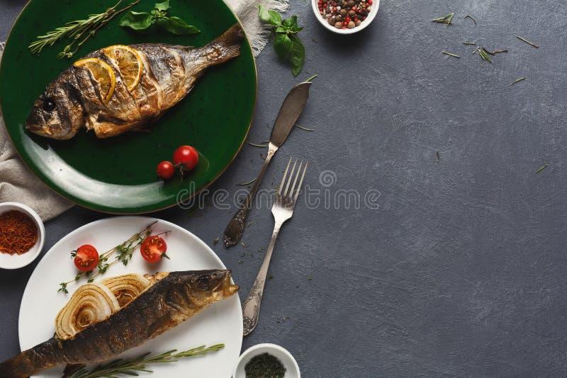 Whole grilled dorado and sea bass on table stock photos