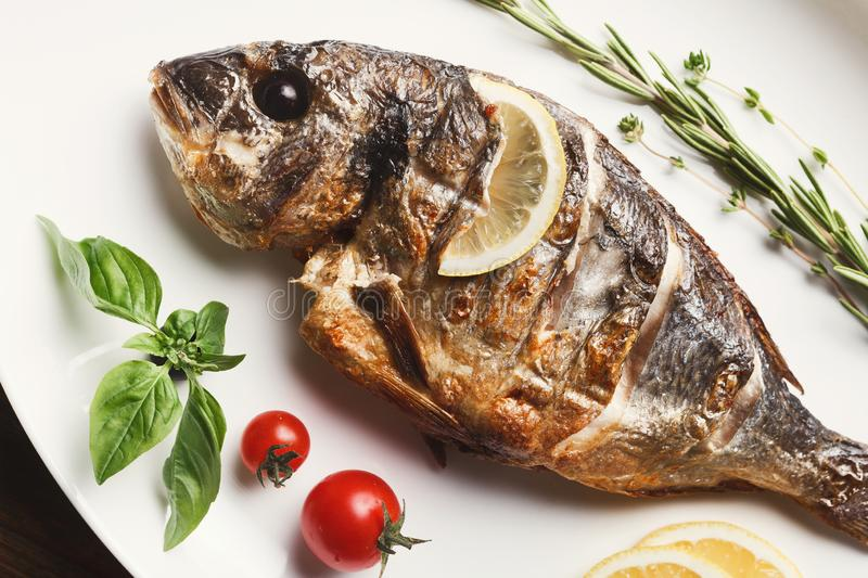 Whole grilled dorado and sea bass on table royalty free stock images