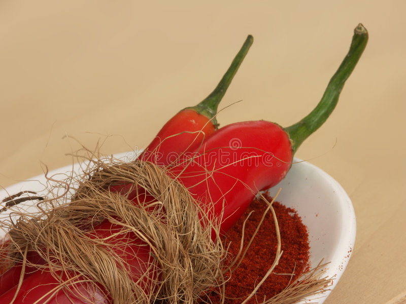 Whole and Ground Red Chili Pepper. Both whole and ground red chili pepper in a dish with garnish stock photos