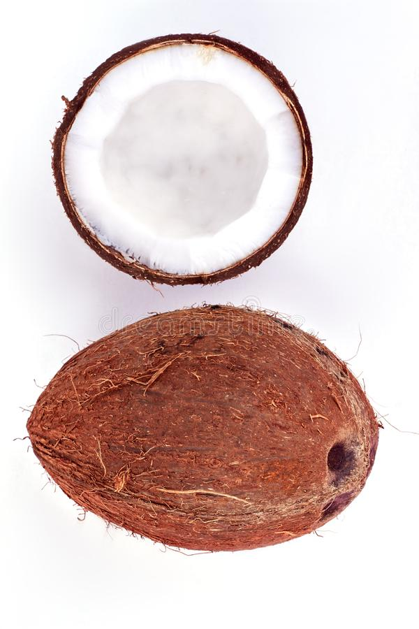 Whole and half coconut, top view. Ripe tropical coconuts on light background. Healthy exotic food royalty free stock image