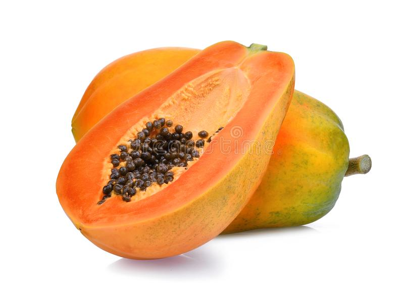 Whole and half of ripe papaya fruit with seeds on white stock images