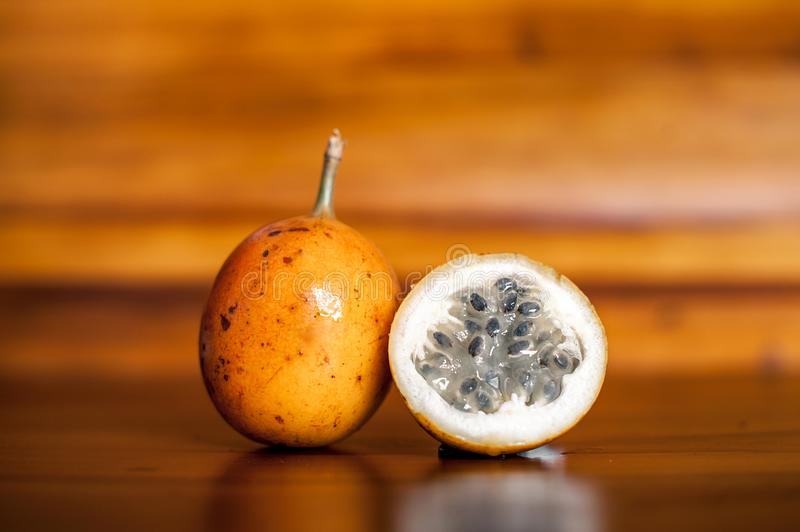Whole and half of ripe yellow passion fruit lying on wooden background. Exotic fruits from Bali stock photos
