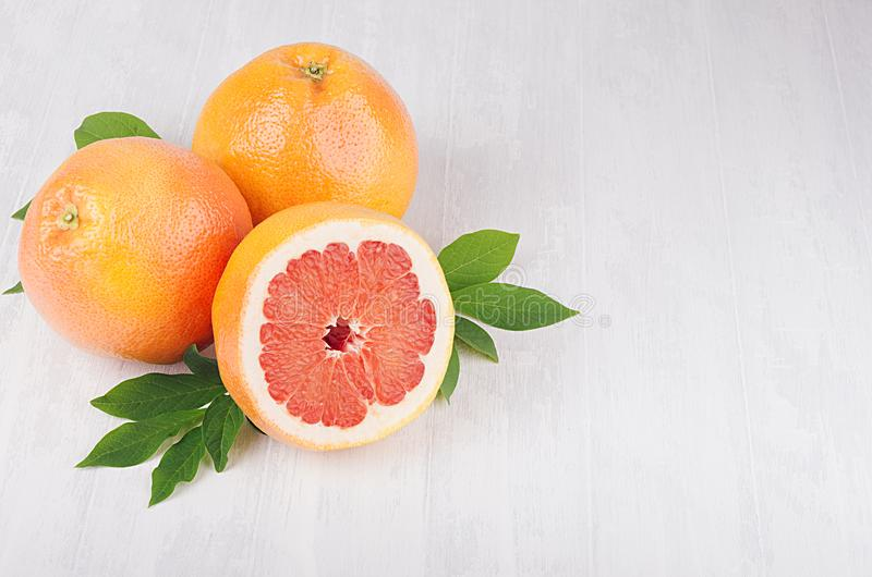 Whole and half slice grapefruits with green leaves on soft white wood background with copy space, top view. Whole and half slice grapefruits with green leaves royalty free stock image