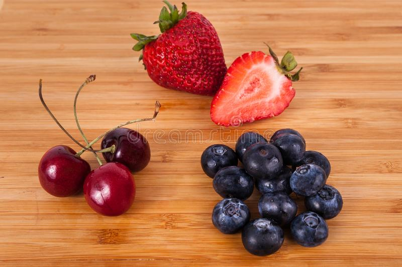 Whole and half strawberry three cherries bunch of blueberries bamboo cuttingboard stock photos