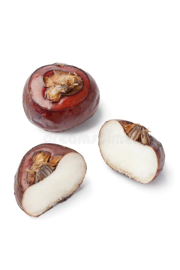Whole and half water chestnuts. On white background stock image