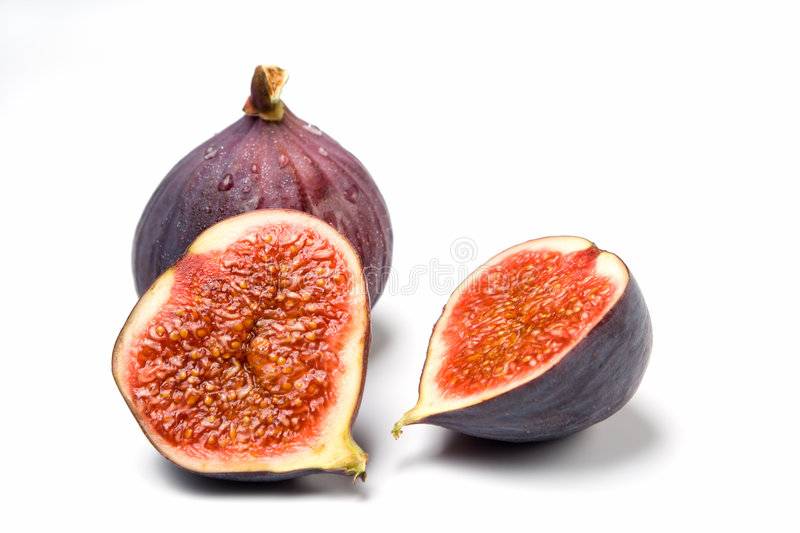 Whole and halved fig isolated. A whole and a halved fig isolated on white background stock image