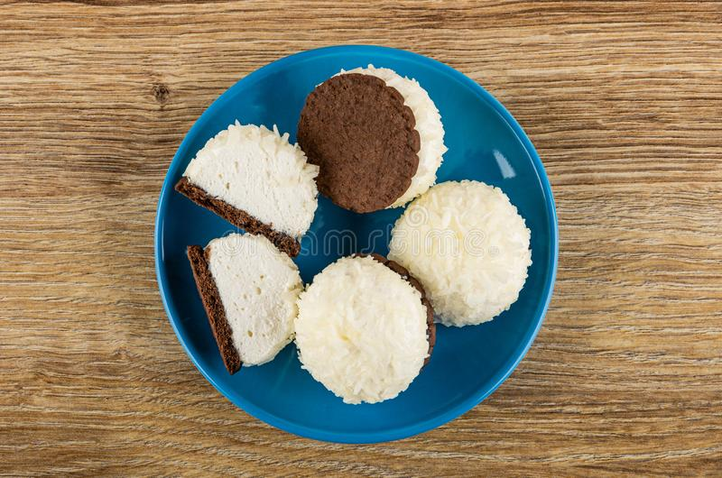 Whole and halves of marshmallows with coconut shaving in saucer on table. Top view. Whole and halves of marshmallows with coconut shaving in blue saucer on royalty free stock image