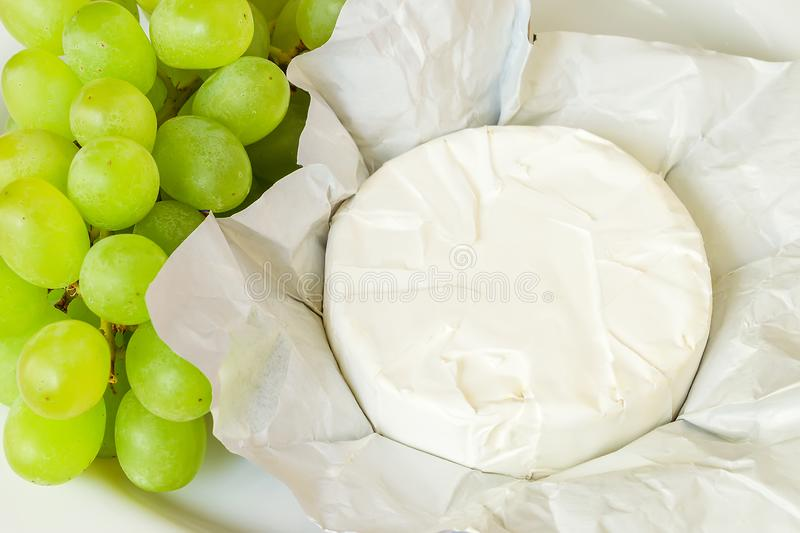 Whole head of camembert in just open paper package and bunch of sweet green grapes in white plate. Soft cheese covered with edible. White mold. Top view royalty free stock image